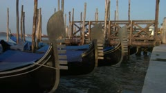 Gondolas bob on their moorings  in the morning light. - stock footage