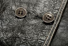 Metal buttons on black leather clothing - stock photo