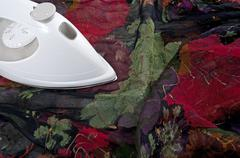 Ironing colorful silk fabric - stock photo