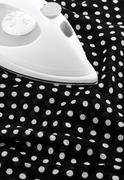 Ironing delicate silky fabric - stock photo