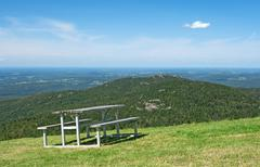 Picnic table in mountains - stock photo