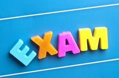 exam word on blue board - stock photo