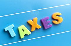 taxes word on blue board - stock photo