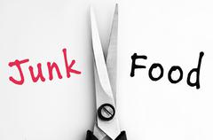Junk and food words with scissors in middle Stock Photos