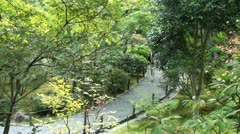 Tourists walk through a beautiful Japanese garden in Kyoto Stock Footage