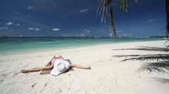 Girl in sun hat relaxing on tropical beach Stock Footage