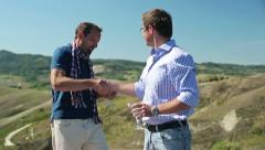 Two male friends celebrating and drinking outdoors, crane shot HD Stock Footage
