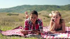 Women with tablet computer and cellphone on picnic, crane shot HD Stock Footage