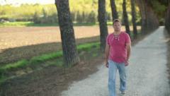 Young man walking on rural road, crane shot HD - stock footage