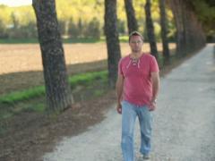 Young man walking on rural road, crane shot NTSC - stock footage