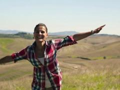 Excited, happy woman turning round on meadow, slow motion NTSC Stock Footage