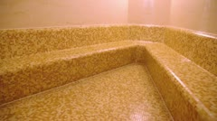 Empty sauna room with tiled wall and seat, shown in motion Stock Footage