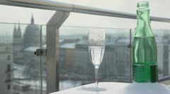 Glass and bottle on balcony at background of Europe square Stock Footage