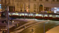 Tramways ride near crossroad with traffic on street at night Stock Footage