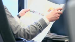 Man reads paper during travel at train, only hands are visible Stock Footage