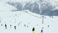 Stock Video Footage of Lot of skiers ride in Alps near ropeway at cloudy winter day