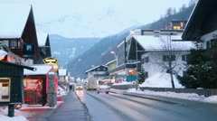 Traffic in small town near mountain with forest at winter day - stock footage