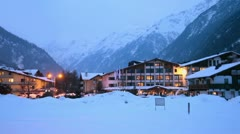 Hotels at ski resort village in mountains at winter evening - stock footage