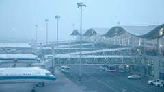 Airliners stand near airport terminals, not flying weather Stock Footage