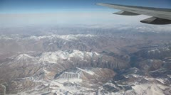 Mountains with some snow at day, view from an aircraft window Stock Footage