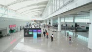 Passengers walk with luggage in airport, shown in motion Stock Footage