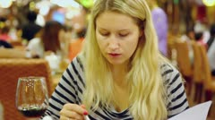 Young woman sits in chair in restaurant and eats first meal Stock Footage