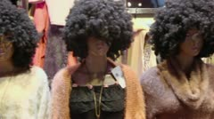 Several mannequins with dark haired curly wigs in disco style Stock Footage