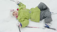 Little girl stands up after she falls on snow during ski ride Stock Footage