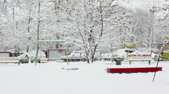 Little girl skiing along yard with trees and cars Stock Footage
