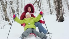 Mother with daughter sit on sled, girl holds ski sticks Stock Footage
