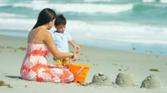 Hispanic mother and children spending summer vacation playing on beach  Stock Footage