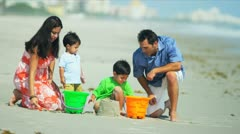 Latin American parents helping sons with sand castles by ocean  - stock footage