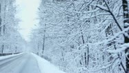 Slow ride by road along forest in snow at winter day Stock Footage