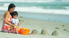 Latin American mother enjoying summer time with son by ocean  Stock Footage