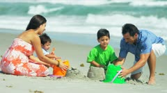 Hispanic parents helping kids with sand castles on beach  - stock footage