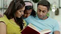 Mother, father and daughter reading a book together at home Stock Footage