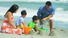 Happy Hispanic family building sand castles on beach  Stock Footage