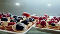 Many tarts with different berrys on showcase in dark cafe Stock Footage