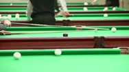 Stock Video Footage of Player uses support for cue and hits billiard game in club