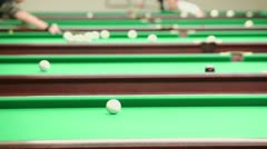People walk around several green tables during billiard game Stock Footage