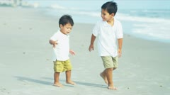 Little Hispanic brothers playing together on beach Stock Footage