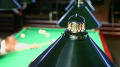 Man plays billiard game in dark club with lamps above table Stock Footage