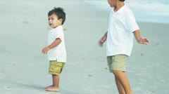 Little Latin American boys walking together on beach - stock footage