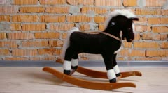 Small toy horse sways on floor in room with brick wall Stock Footage