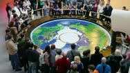 People stand around earth map with sphere pendulum sways above Stock Footage