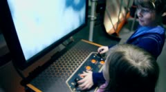 Two kids play with virtual space apparatus in Planetarium Stock Footage