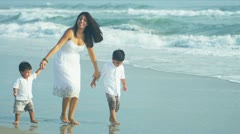 Hispanic  parent walking with kids on beach dressed in white  - stock footage