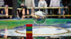 Metal sphere pendulum sways near colorful toy blocks - stock footage