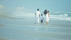 Latin American family spending holiday on beach playing in ocean surf  - stock footage