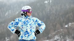Skier in goggles talk on handheld transceiver against forest Stock Footage